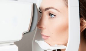 Sweet young adult brunette looking at eye test machine in ophthalmologist